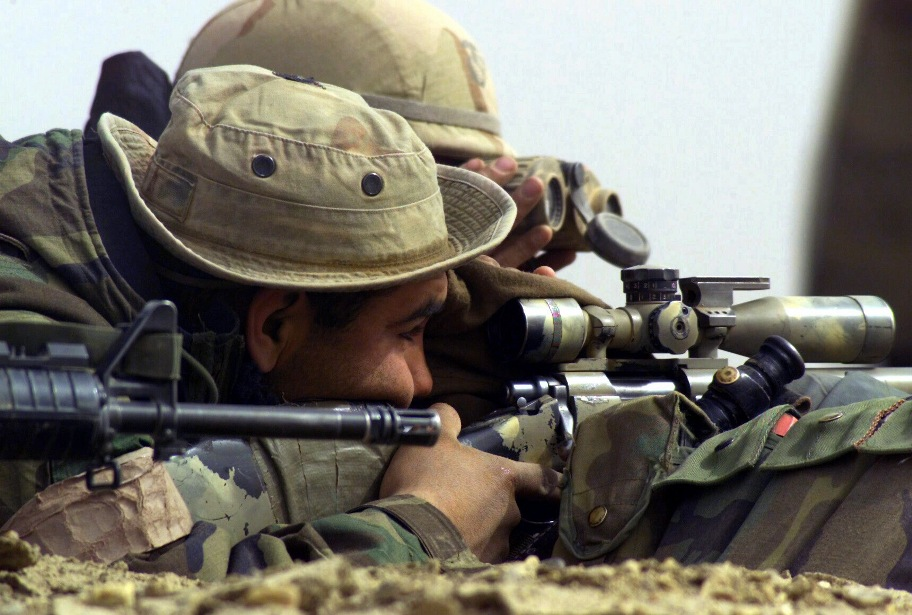 US Marine Corps (USMC) assigned as a Sniper with 1st Battalion, 4th Marine Regiment, Regimental Combat Team 1 (RCT-1), sights through the telescope mounted atop his 7.62mm M40A1 sniper rifle. US Navy (USN) Hospitalman (HN) Clint Sprabary acts as his spotter, at Al Shur, Iraq, during Operation IRAQI FREEDOM. Photo: Public Domain