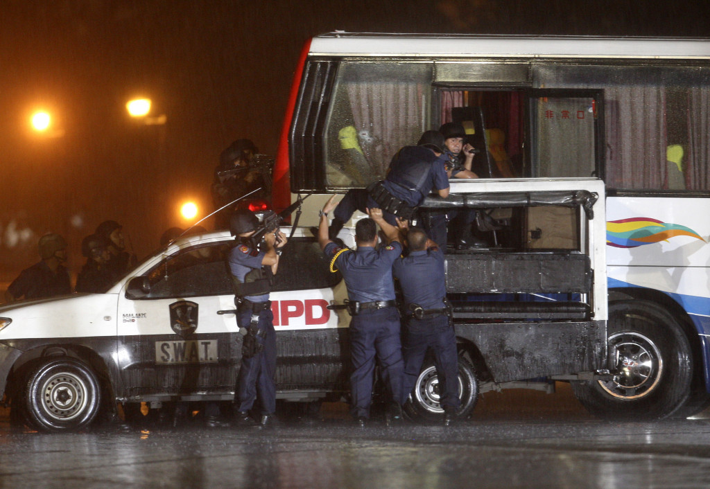 Police and SWAT members assault a tourist bus to rescue hostages at Manila's Rizal Park Monday Aug.23, 2010 in Manila, Philippines. Rolando Mendoza, a dismissed policeman armed with automatic rifle, seized the bus in Manila Monday with 25 people aboard, mostly foreign tourists in a bid to demand reinstatement, police said. Mendoza was killed along with an undetermined number of hostages. (AP Photo/Bullit Marquez)